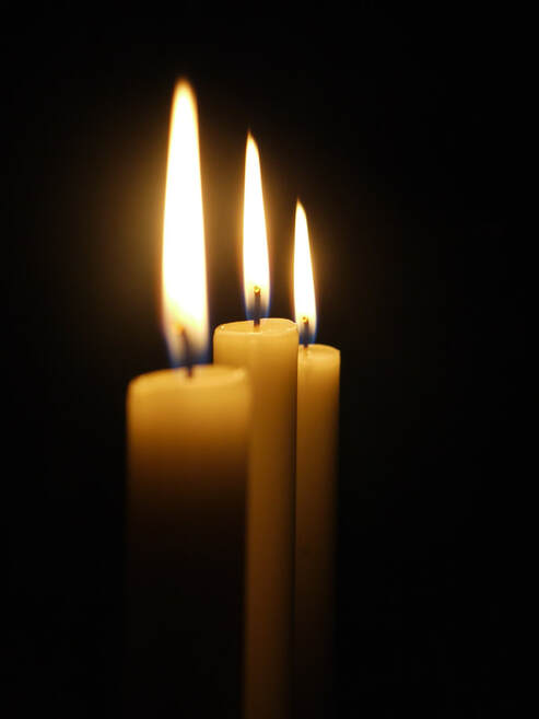 Picture of three cream colored candles with flames on a black background.
