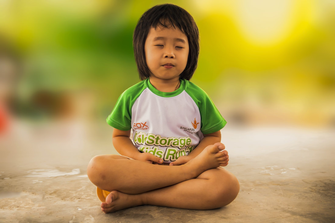 Picture of a child sitting in easy pose for yoga.