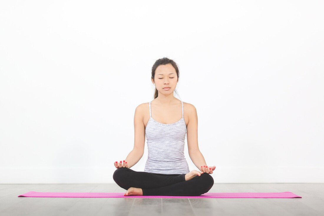 Picture of female sitting on a pink yoga mat in easy pose for yoga.